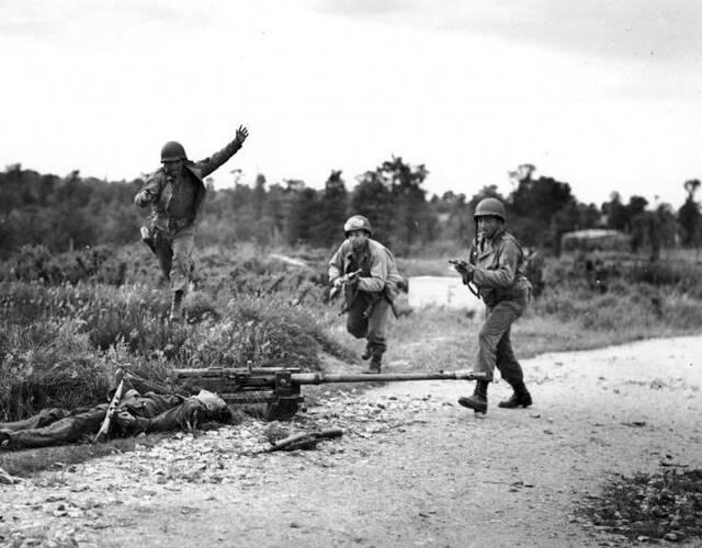 美国大兵从一名死亡的德国士兵旁跑过。