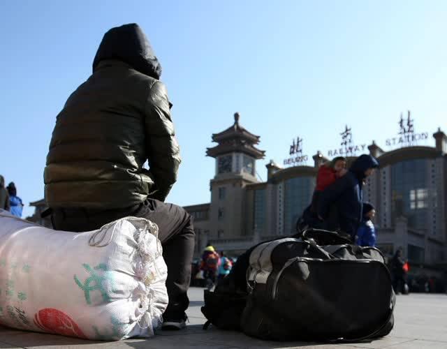 火车站广场一角,一位安静的坐在行李上,边晒太阳边看着验票进站的庞大队伍。