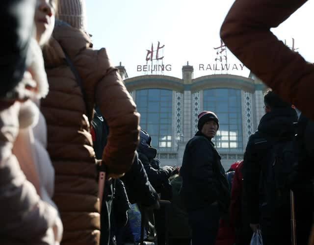 """即将结束这一年的""""北漂""""生活,来到火车站哪曾想到最后一关也这么难。图为一位旅客焦急的排着队,不时回望身后的人群,一脸惆怅。"""