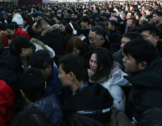"""春节又近,""""北漂人""""似乎已经平静不激动的心情,家的吸引力让他们归心似箭。春运进入第四天,""""成群结队""""也可以说是""""蜂拥而至"""",回家旅客来到火车站,不约而同围堵在验票口,依次进站,由于数量众多,人群中难免你拥我挤。图为在火车站外广场的验票口,排着数十米长的队伍,一位美女前后""""夹击"""",要被挤哭。"""