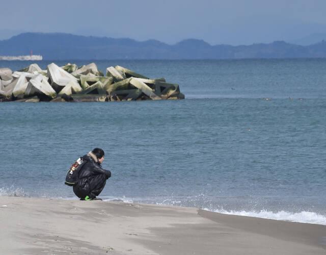 一名市民蹲在海边,遥望远方