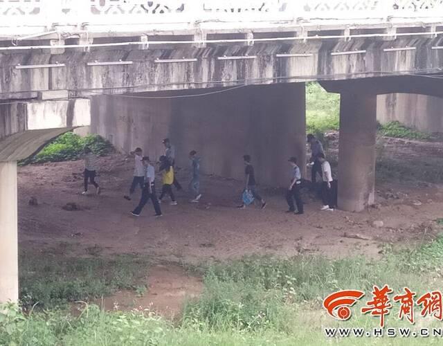 下午3时许,公安渭滨分局接到线索,金陵桥下也有传销人员活动。警察赶到后,发现在桥墩下的河床上,十余名青年男女在生火做饭,河床两旁都是河水。警察向桥下人员喊话,让他们上岸,否则有危险。但这些人员无动于衷,警察只好涉水悄悄进入河床,将他们当场堵截住带离。