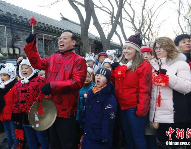 """2月3日,第十届春官报春活动在北京东四九条胡同举行。穿着传统服饰的春官春吏以及社区小朋友在近七百年历史的胡同里高喊着:""""春来了,春到了!"""",并给街坊邻里分发福字、对联等。中新社记者 杜洋 摄"""