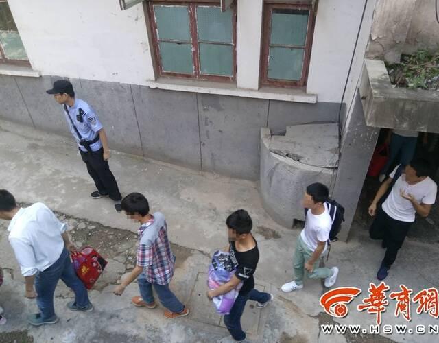 长青路一处住宅楼内的涉嫌传销人员被警方带离。
