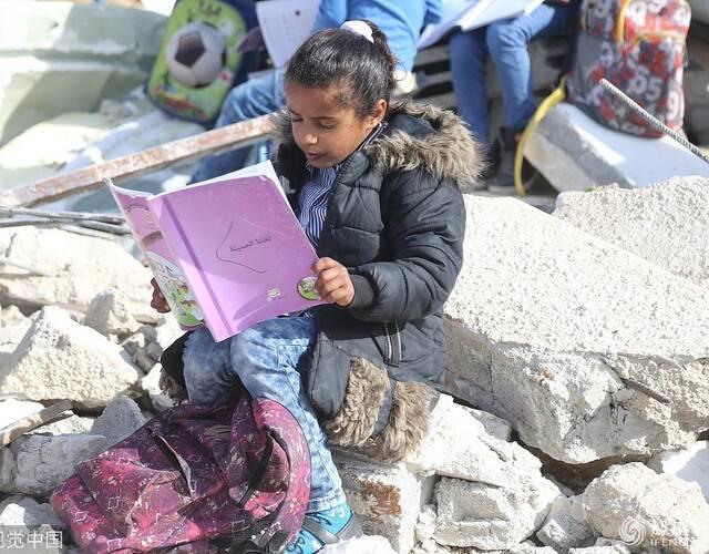 2018年2月4日,耶路撒冷,以色列部队因Abu al-Nuwar小学缺乏办学执照强拆了教室,巴勒斯坦小学生手持巴勒斯坦旗帜,在校园的废墟上继续学习。Issam Rimawi/视觉中国