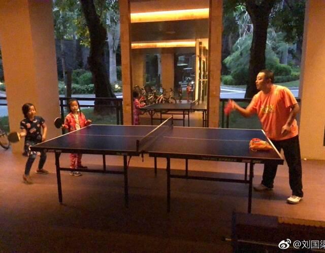 刘国梁与双胞胎女儿练习乒乓球