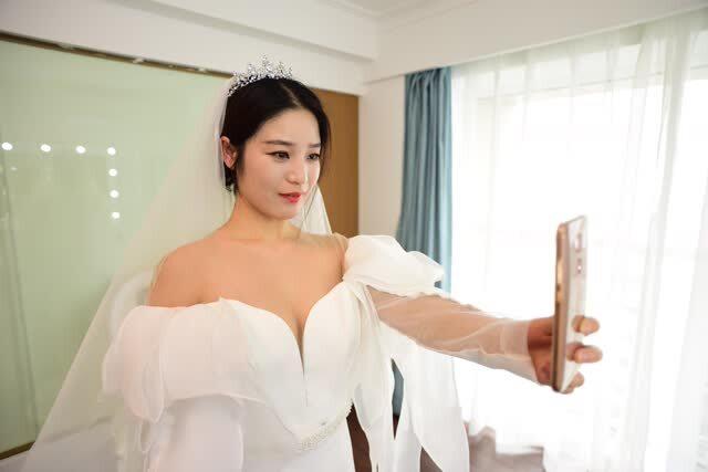 秦玉瓶决定去照一张婚纱照,最直接地拒绝众多追求者。摄影师是她的朋友,免费拍摄。这张照片可以用简陋来形容:白色的背景是窗帘,所谓的婚纱是一件借来的、十分不合身的白裙子,而头纱则是包裙子的布套。她的长发被简单地绑起来,脸上的妆也是自己动手,没有双眼皮贴,没有假睫毛,更没有腮红和暗影粉,她说:妆也是用手画的,因为没有化妆工具。照片虽然是低配,但是一袭洁白的秦玉瓶确是挡不住的动人。