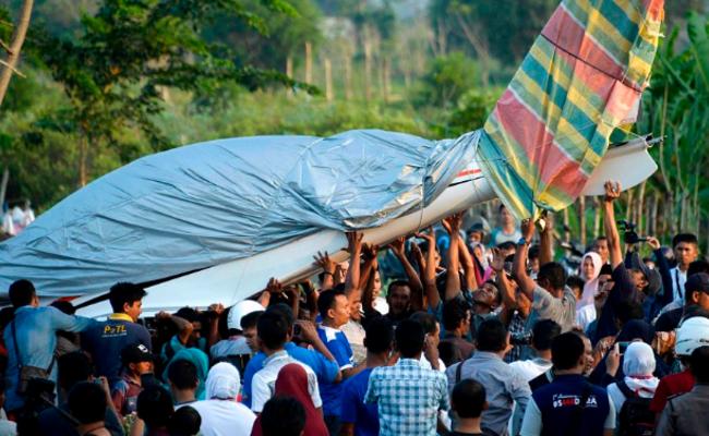 印尼官员驾机故障迫降 村民合力抬飞机
