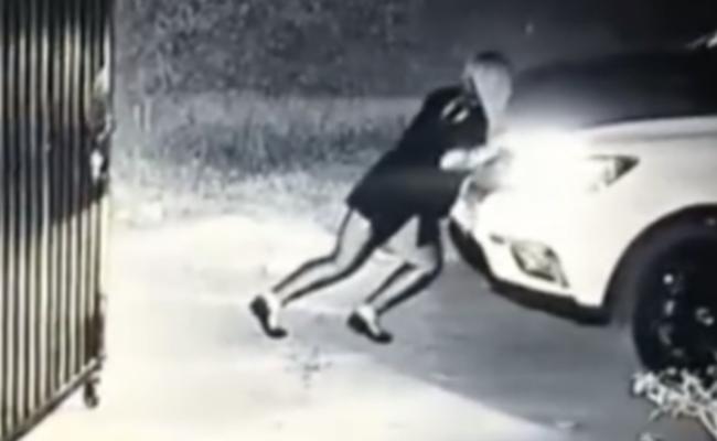 女司机忘拉手刹溜车 用身体将车顶回
