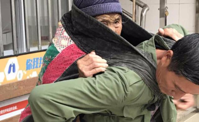男子用婴儿背带背老母亲看病 刷屏朋友圈|组图