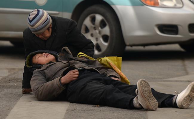 老母亲守护晕倒儿子 怕被误解拒绝帮助