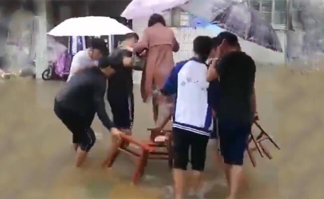学生雨中持凳帮老师垫脚趟水