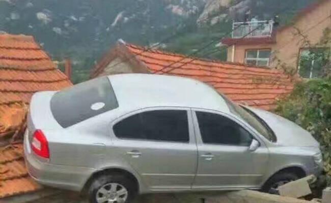 青岛一司机倒车太猛 冲上村民屋顶