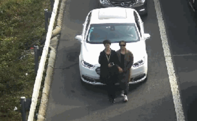 为占用应急车道 两女子手挽手遮挡车牌|组图