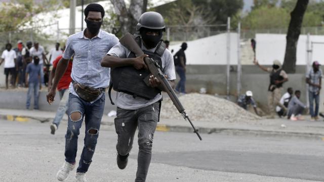 实拍:海地警察上街开火发泄不满 路人抬着伤者惊慌逃走