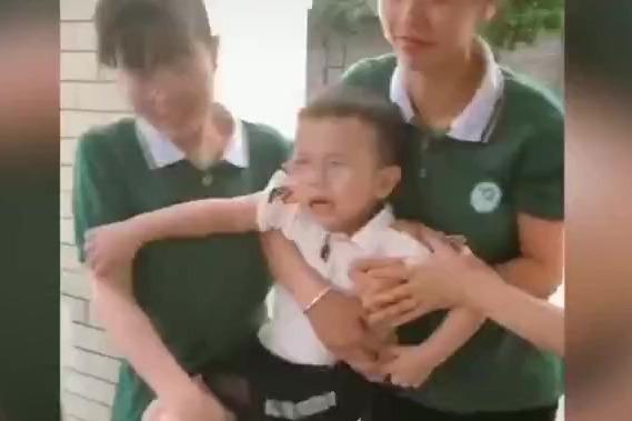 小朋友#不想去幼儿园老师连拖带拽扛进门#:好不容易开学了还想跑