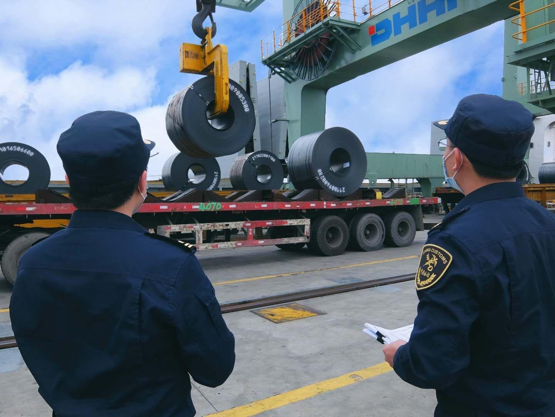 图为:湛江海关关员在船边验放出口钢卷